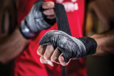 MMA fighter tightening tape around his hands