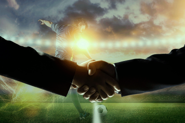 two football agents shaking hands in front of a football stadium during transfer winter market of 2021